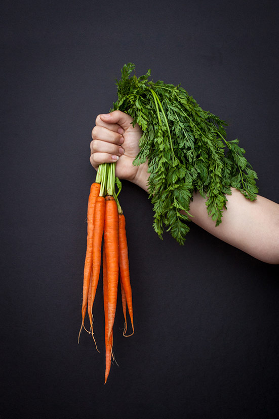 Holding a bunch of fresh picked carrots.